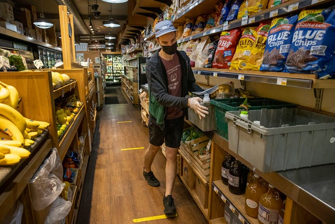Grocery clerk Matt Sawyer organizes containers used to keep home-delivery and curbside pickup items together at Weavers Way Co-op in Philadelphia's Mount Airy section. (Alejandro A. Alvarez/The Philadelphia Inquirer/TNS)