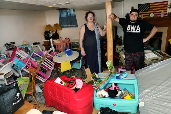 Sierra Chapman and her fiance, Donald LeMay, stand in the basement of their flood-damaged Reynoldsburg home on Wednesday. Everything in the basement, including their children's toys, is a total loss, they said.