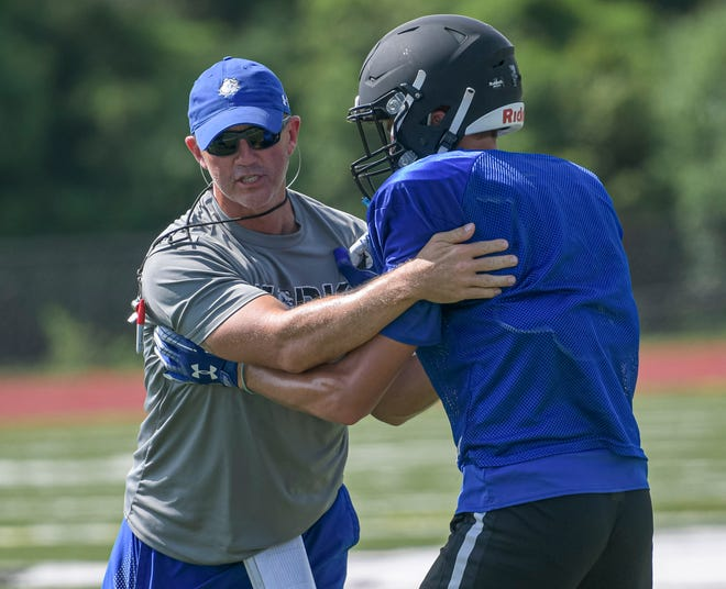 MDCA head coach Mike Kintz works with a player during practice Tuesday at Mount Dora Christian Academy in Mount Dora. [PAUL RYAN / CORRESPONDENT]