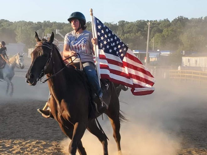 Madeline Mazer, who is a part of the 9/11 drill team and a student at Chippewa High School, practices holding an American flag as part of their routine for the opening ceremony at the Wayne County Fair on Sept. 11. The team was started after several students approached 4-H adviser Mindy Browning with the idea to start the team to honor service members and first responders.