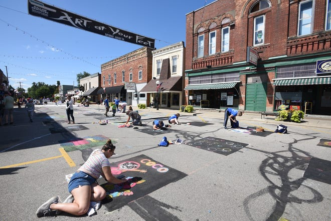 Artists of all ages and levels of artistic ability line South Lane Street in downtown Blissfield during the 2019 Art at Your Feet street art festival, presented by the Schultz-Holmes Memorial Library. The art festival returns to South Lane Street Saturday, Aug. 21, after being conducted virtually in 2020.