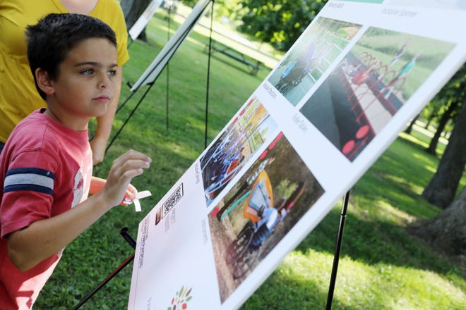 Henry Stevens, 9, of Burlington looks over a selection of park features being considered Tuesday during a public input session for the Dankwardt Park playground's upcoming replacement at the park in Burlington. The public was invited to listen to a representative of the Confluence design firm, take a public survey and talk with staff members about what they would like to see incorporated into the new playground's design.