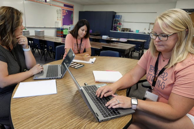 Mediapolis second grade teachers Abby Housman, left, Kari Stephens, center, and Laura Eldon, right, review their collaborative learning schedules Wednesday in Houseman's classroom at Mediapolis Elementary School. Students will return to classes starting Monday.