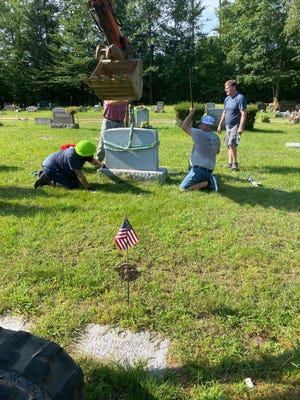 Volunteers work to lift a headstone back into place after Pine Grove Cemetery was badly vandalized last week.