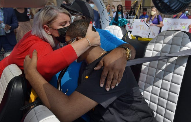 Andrew Jackson High School teacher Jennae Tuzzolo hugs Talen Birt during his visit to his school Wednesday morning.