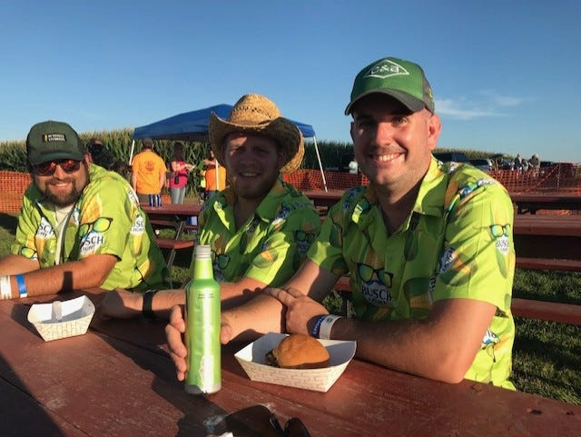 Three friends enjoy a sandwich and a cold brew during the Back Roads Music Festival