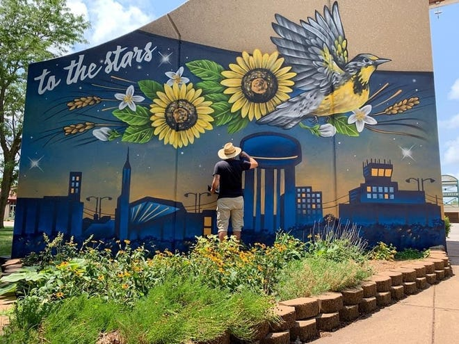 Brady Scott paints a mural on the visitor's center at the Kansas State Fair.