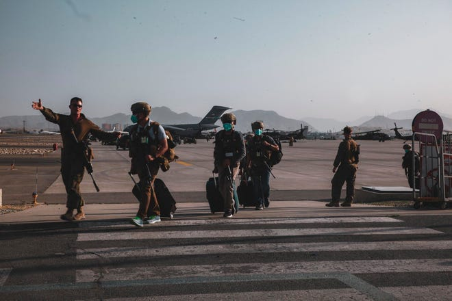 A Marine assigned to the 24th Marine Expeditionary Unit escorts Department of State personnel to be processed for evacuation at Hamid Karzai International Airport, Kabul, Afghanistan, Aug. 15, 2021.