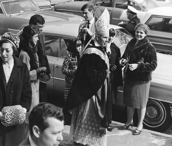 In this file photo from 1968, Bishop Fulton J. Sheen, center, greets some Peoria friends shortly after celebrating Mass at St. Patrick's Church while commemorating the parish's 100th anniversary.