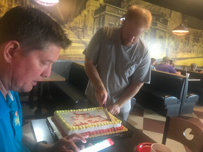 Clint McBroom cuts into an anniversary cake marking one year since a men's group began having a weekly lunch at Gurtys, 221 E. 12th.
