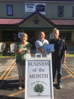 Cathy and Dave Cooper receive the Business of the Month Award for August from Jim Crane, president of the Farmington Chamber of Commerce. Their business, Dave's Diggs, has a gift shop and outdoor furniture and sheds.
