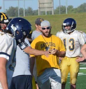 New head coach, DJ Szymoniak, works with his team during preseason practices.