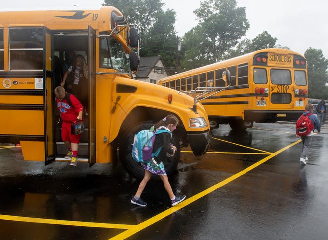 Students exit their school buses on the first day of school at West Main Elementary School in Ravenna. Most students in Ravenna got an unexpected day off on Wednesday because of the high temperatures expected.