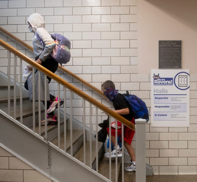 Students at West Main Elementary School in Ravenna wear face coverings as they climb the stairs to the classrooms.