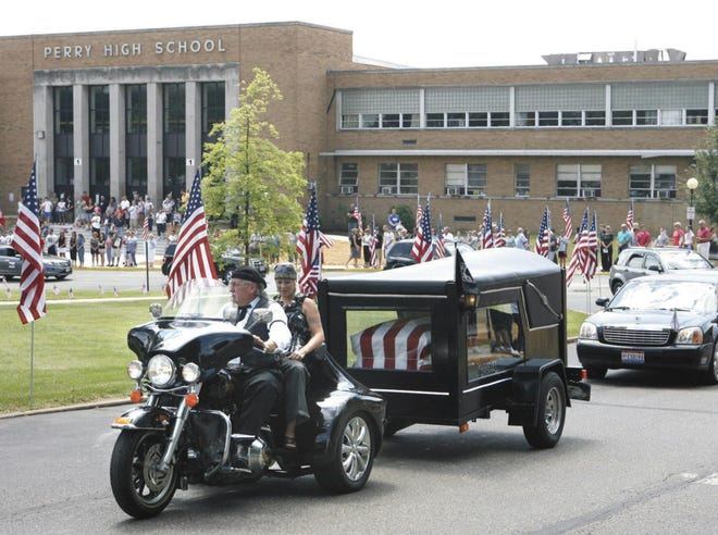 A motorcycle pulling the casket of Marine Corps. Sgt. Daniel J Patron leads the way as the processional passed through Perry High School on the way to the cemetery in 2011.