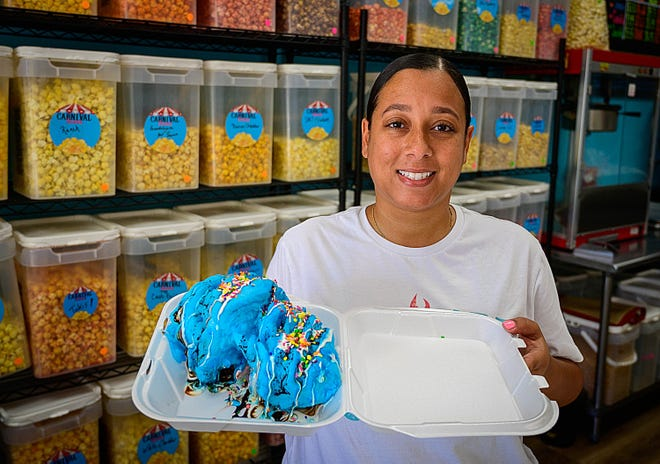 Carnival Sweets co-owner Jerrica Anderson holds a cotton candy burrito, which is made of three scoops of ice cream wrapped in cotton candy, topped with marshmallow fluff, chocolate syrup, multi-colored sprinkles and Nerds candies in her store in St. Augustine on Wednesday.