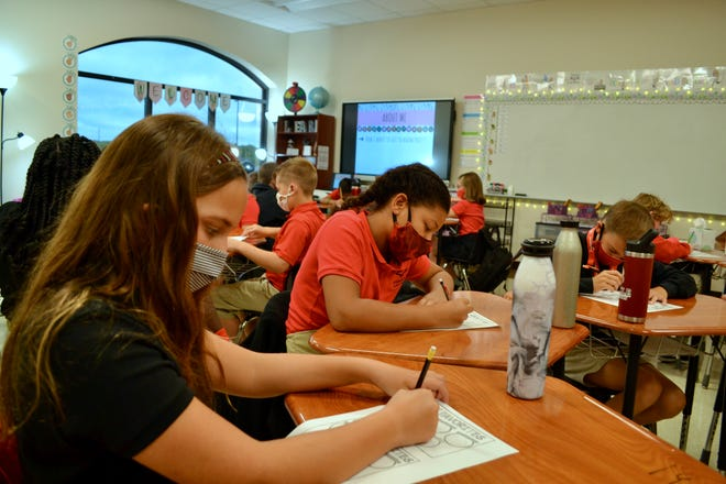 """Stephenie Causey's fifth-grade class fill out """"about me"""" forms to start the first day of school."""