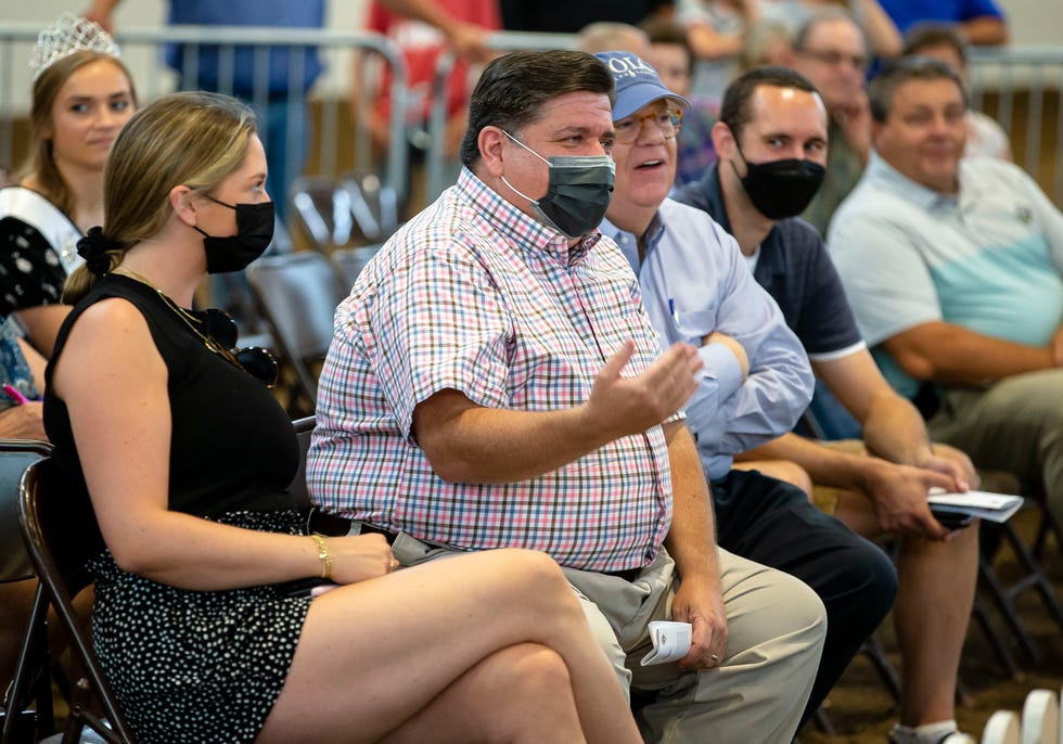 Illinois Gov. JB Pritzker signals that he is out of the bidding war with Illinois first lady MK Pritzker for the grand champion steer during the Governor's Sale of Champions in the Coliseum of Champions during the 2021 Illinois State Fair at the Illinois State Fairgrounds in Springfield on Tuesday.