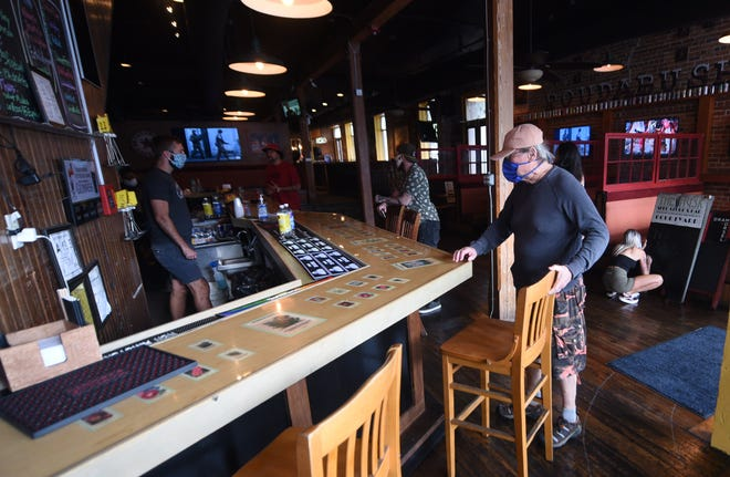 Lauri Buchana, right, takes a seat at the bar just after The Husk opened in downtown Wilmington, N.C., May 22, 2020.