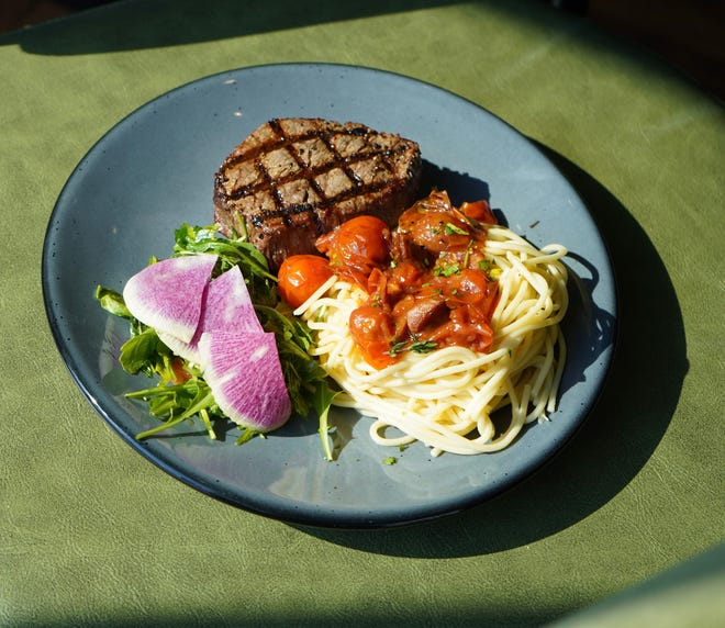 The filet is an 8-ounce steak served with pancetta, blistered cherry tomatoes and Aglio e olio.
