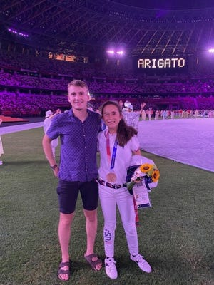 Former St. John's High standout Jon Green and Molly Seidel are all smiles after the medal ceremony, in which Seidel received bronze after her performance in the Olympic women's marathon.