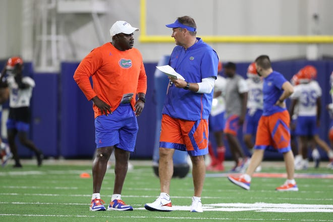 Florida coach Dan Mullen, right, listens to assistant coach Wesley McGriff during a recent practice.