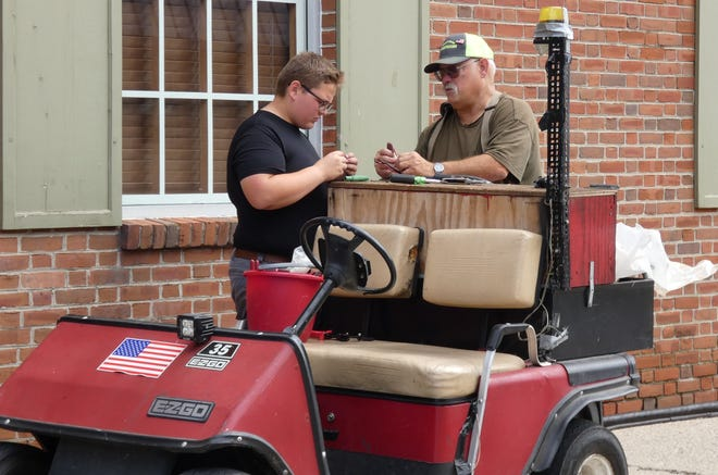 """Electrician Jim Rinker, right, a longtime Bratwurst Festival volunteer, works withhis grandson and """"apprentice in training,""""Isaac Beck, as preparations for this year's festival continue Wednesday morning onWest Rensselaer Street."""