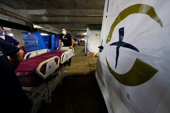 The Samaritan's Purse's logo stands out as staff roll a portable bed to one of four wards that are part of the 32-bed Samaritan's Purse Emergency Field Hospital set up in one of the University of Mississippi Medical Center's parking garages, Tuesday, Aug. 17, 2021, on the Jackson, Miss., campus. The field hospital, an outreach program that is part of a nondenominational evangelical Christian organization, joins a 20-bed field hospital and monoclonal antibody clinic opened by the U.S. Department of Health and Human Services at UMMC in response to the rising number of COVID-19 cases in the state.