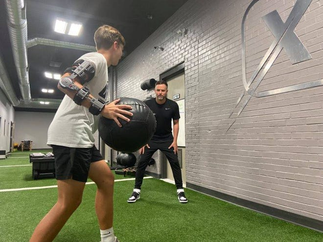 Heath Ladd works with an athlete rehabbing an arm injury last week at Dynamix Physical Therapy in Milan.