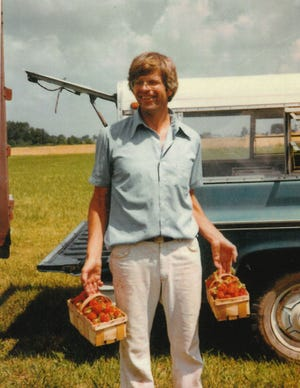 Howard Crum holding strawberries on his farm on Marion-Edison Road in the mid-1980s. He bought the 150-acre farm from his mother in 1977.