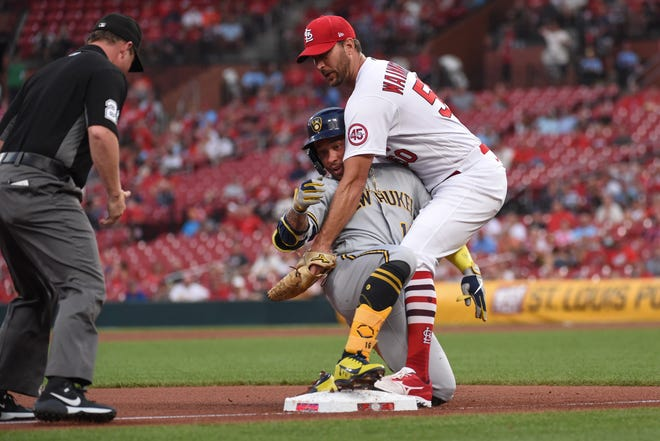 Kolten Wong of the Brewers slides into third base ahead of the tag of Cardinals pitcher Adam Wainwright after hitting an RBI double and moving up on an error in the second inning.