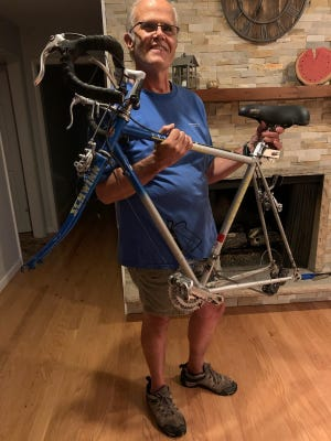 Abbey's father, Bill Stirgwolt, shows off the remainder of her stolen bike, Hwin, that he found.