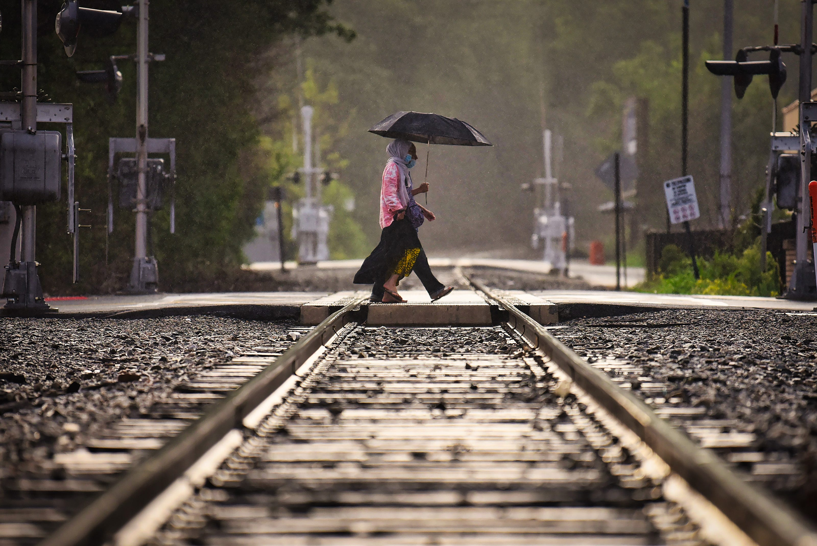 As light rain falls, two pedestrians with an umbrella cross the railroad tracks near the corner of Mercer and State streets in Hackensack on 08/08/21.