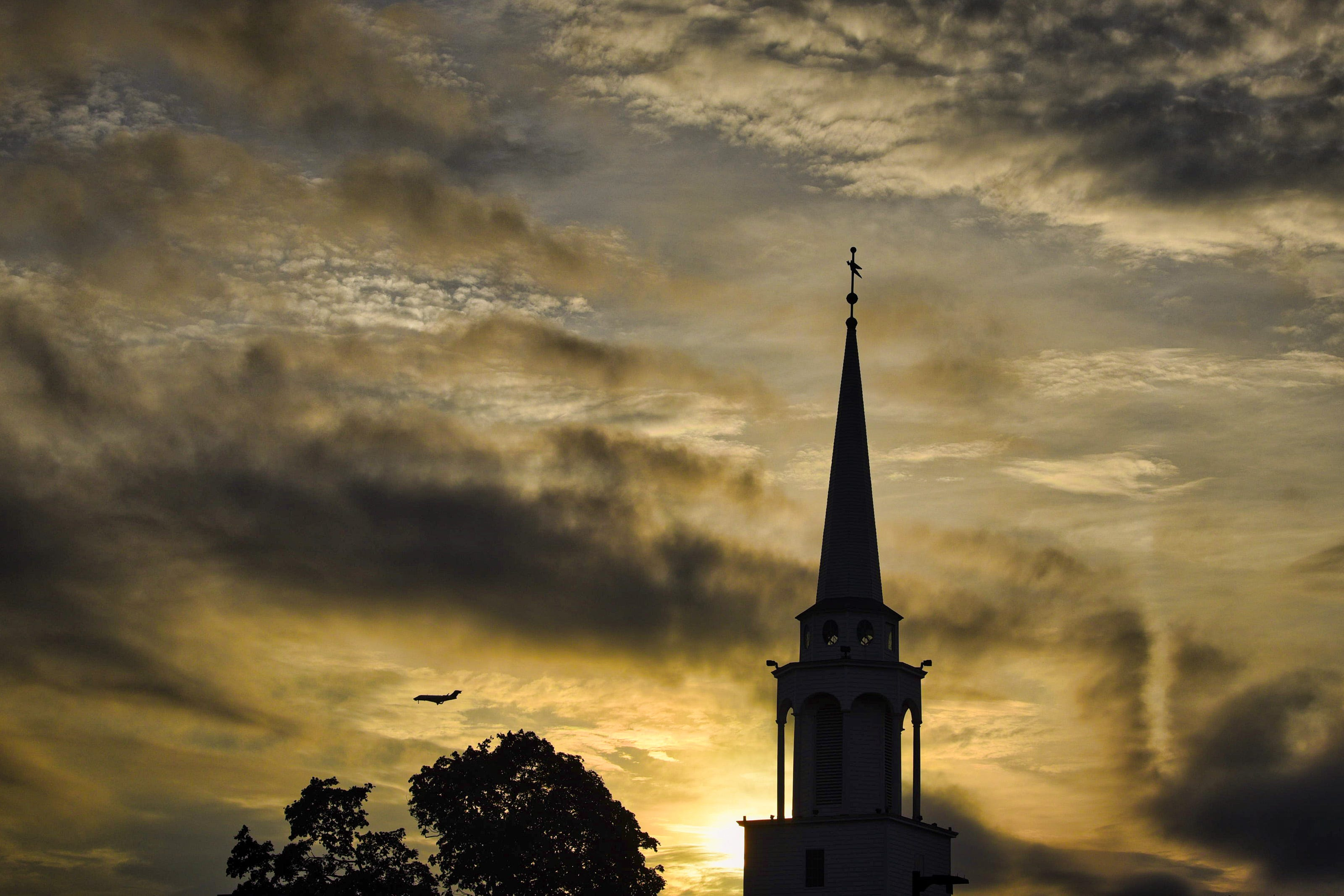 The First Presbyterian Church at 64 Passaic Street is silhouetted against a dramatic evening sky with the sun setting, as a jet flies in the background over Hackensack on 08/17/21.