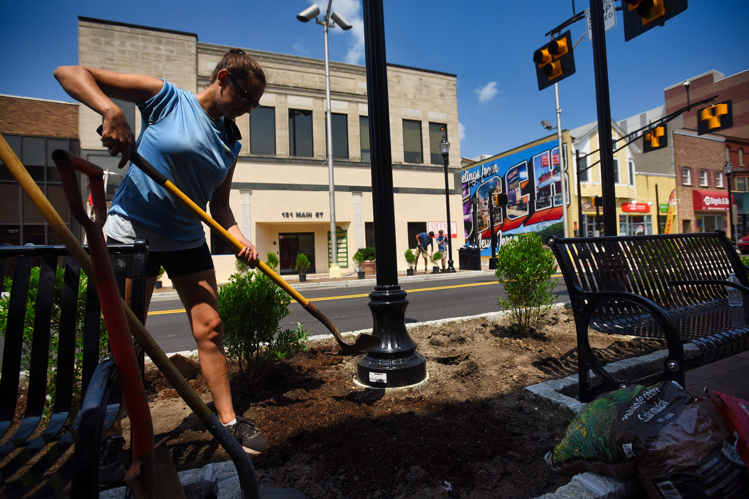 Alex Rakoczy, a Horticulturist, from Cerbo's in Parsippany, digs the ground to plant flowers as she and other co-workers (across the street) work for the city improvement project along Main Street in Hackensack on 07/18/21.