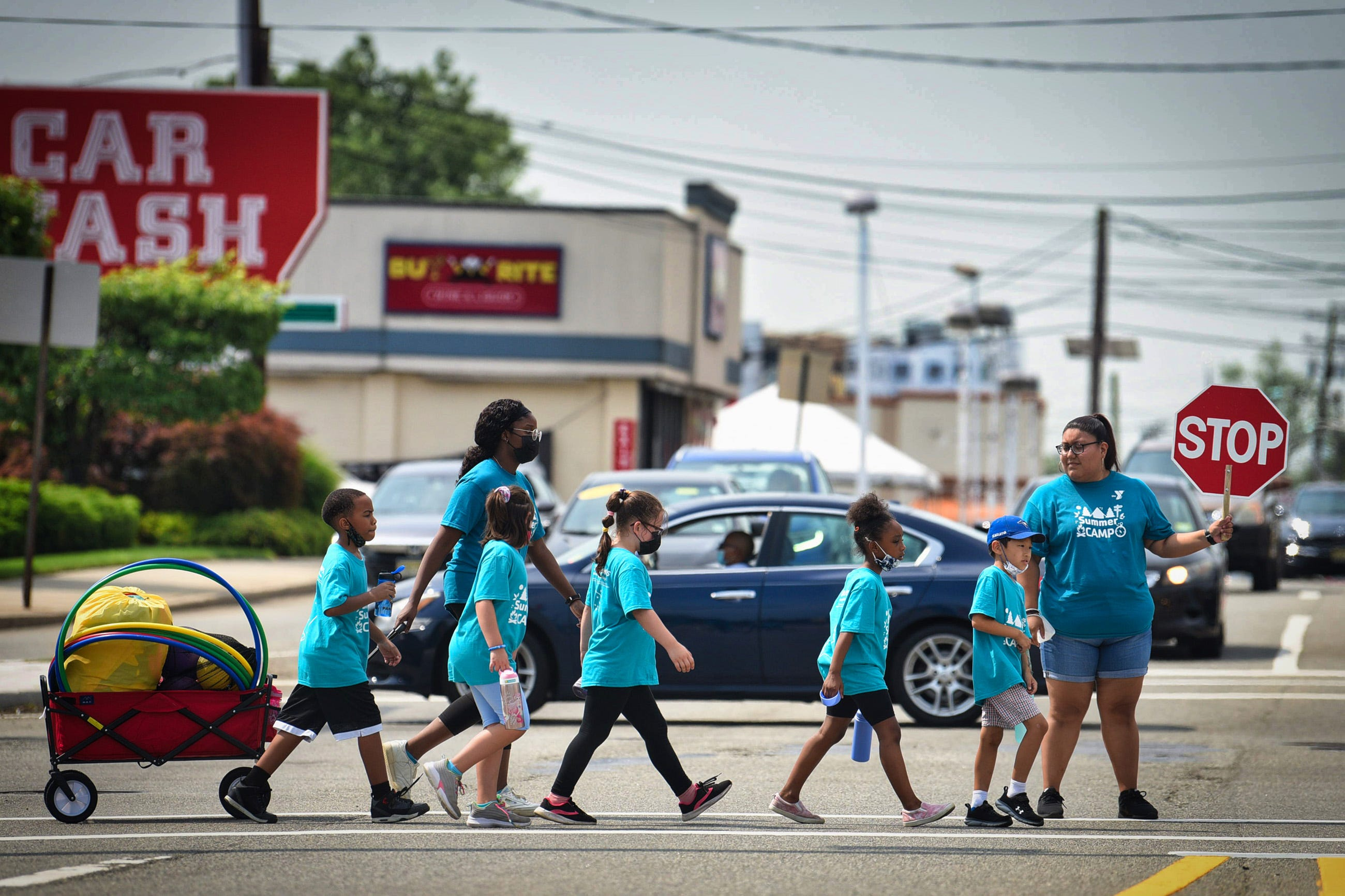 A crossing guard holds back traffic as summer camp students cross at the intersection of River and  East Anderson Streets in Hackensack on 07/18/21.
