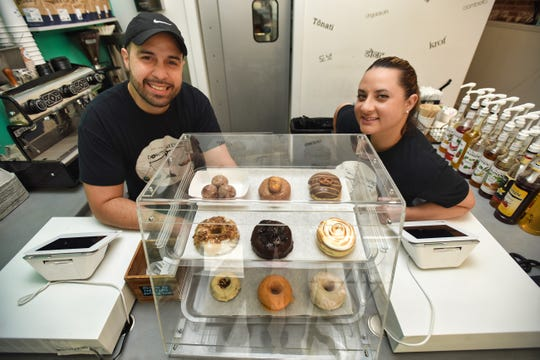 Co-owners, Eddie Alfonso, L, and Flavia Carballo,R, pose for a photo with their displayed donuts at The LoDG in Jersey City on 08/18/21.