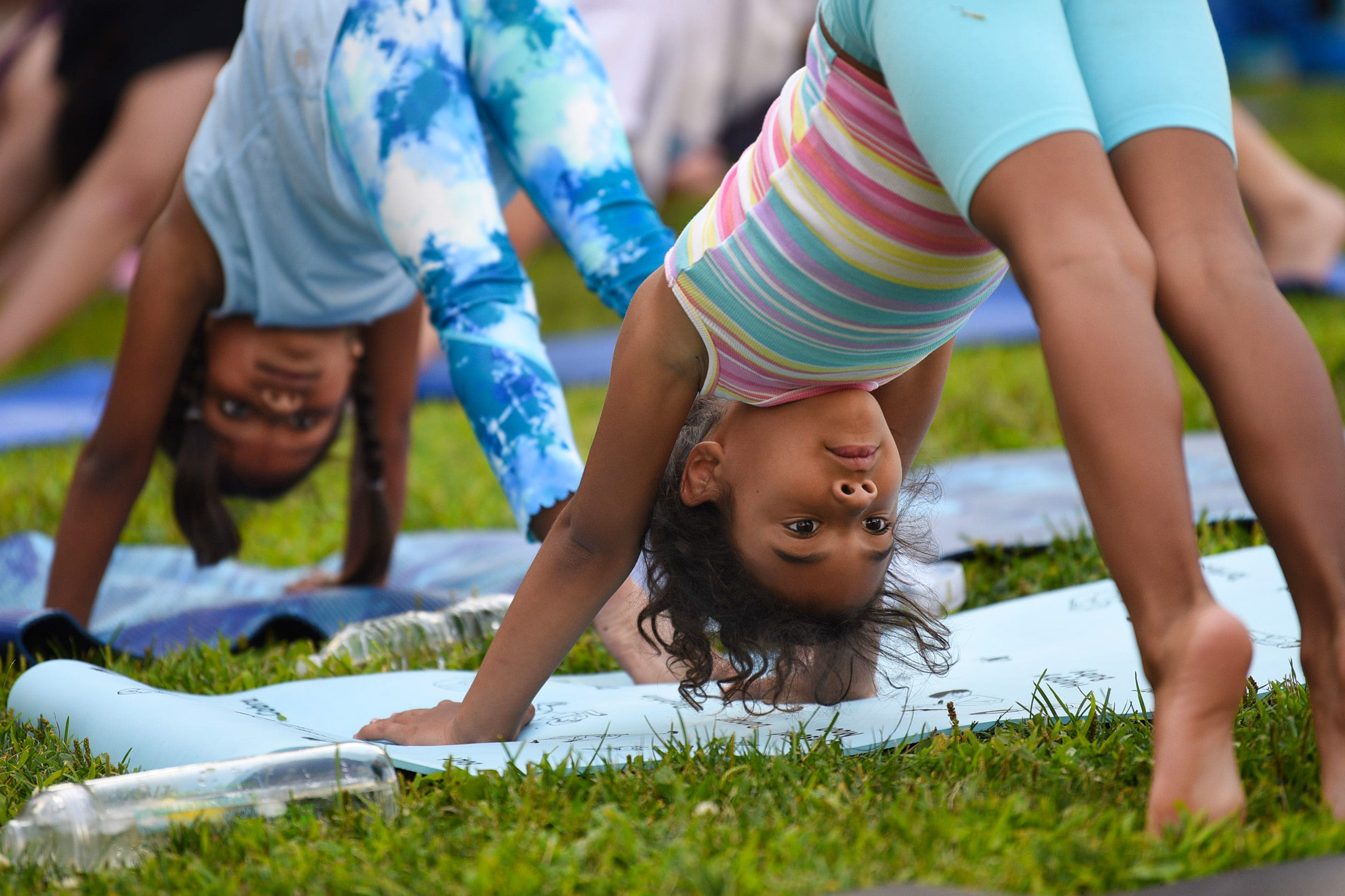 Val, left, 6, of Garfield, and Bri, right, 6, of Hackensack, follow the instructions from yoga instructor Melissa Varjan during sunset yoga in Atlantic Street Park just outside of the Hackensack Performing Arts Center on 08/02/21.