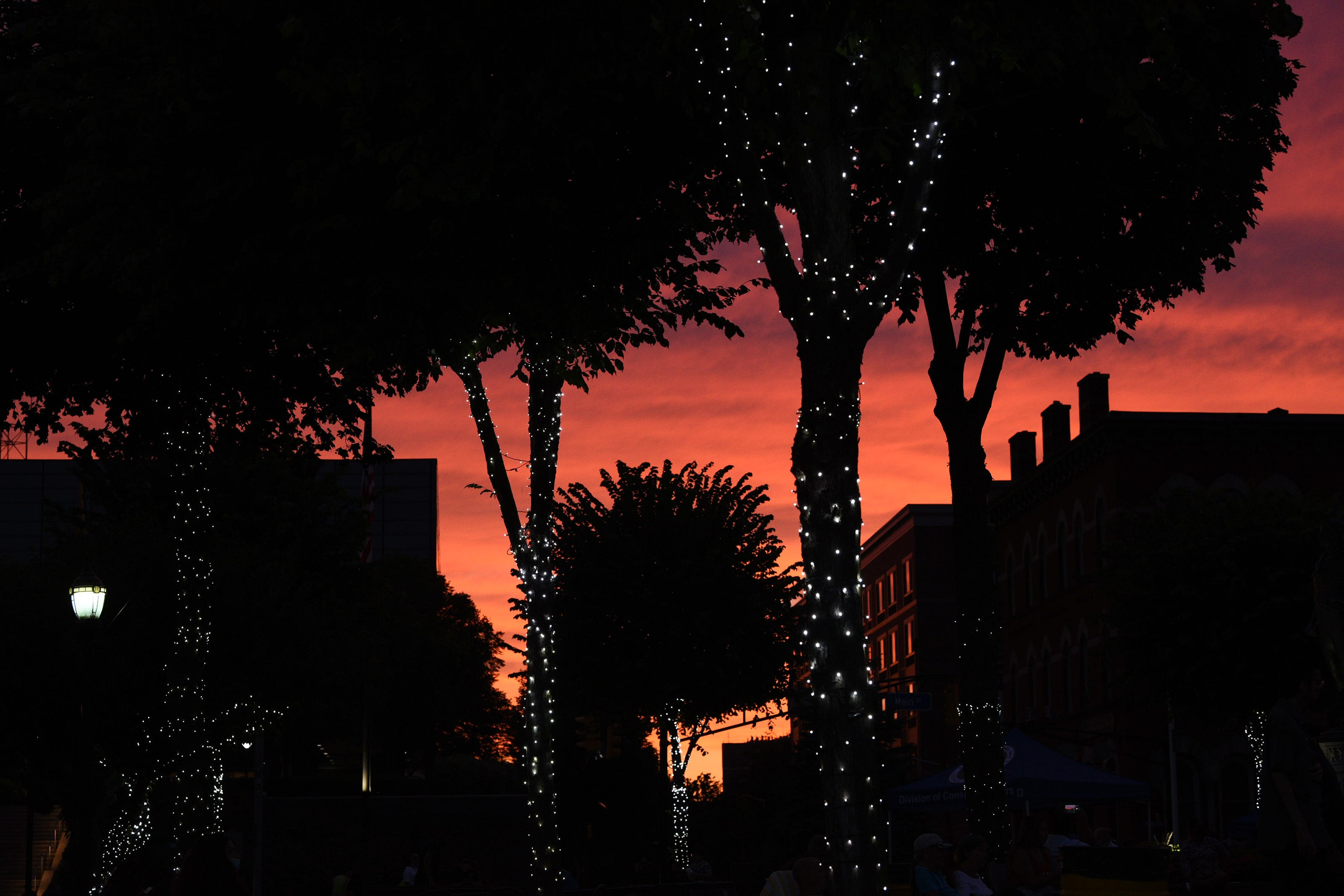 The dramatic evening sky creates a silhouette of trees and buildings on The Green in Hackensack during the free Summer Concert series hosted by HACPAC on 08/03/21.