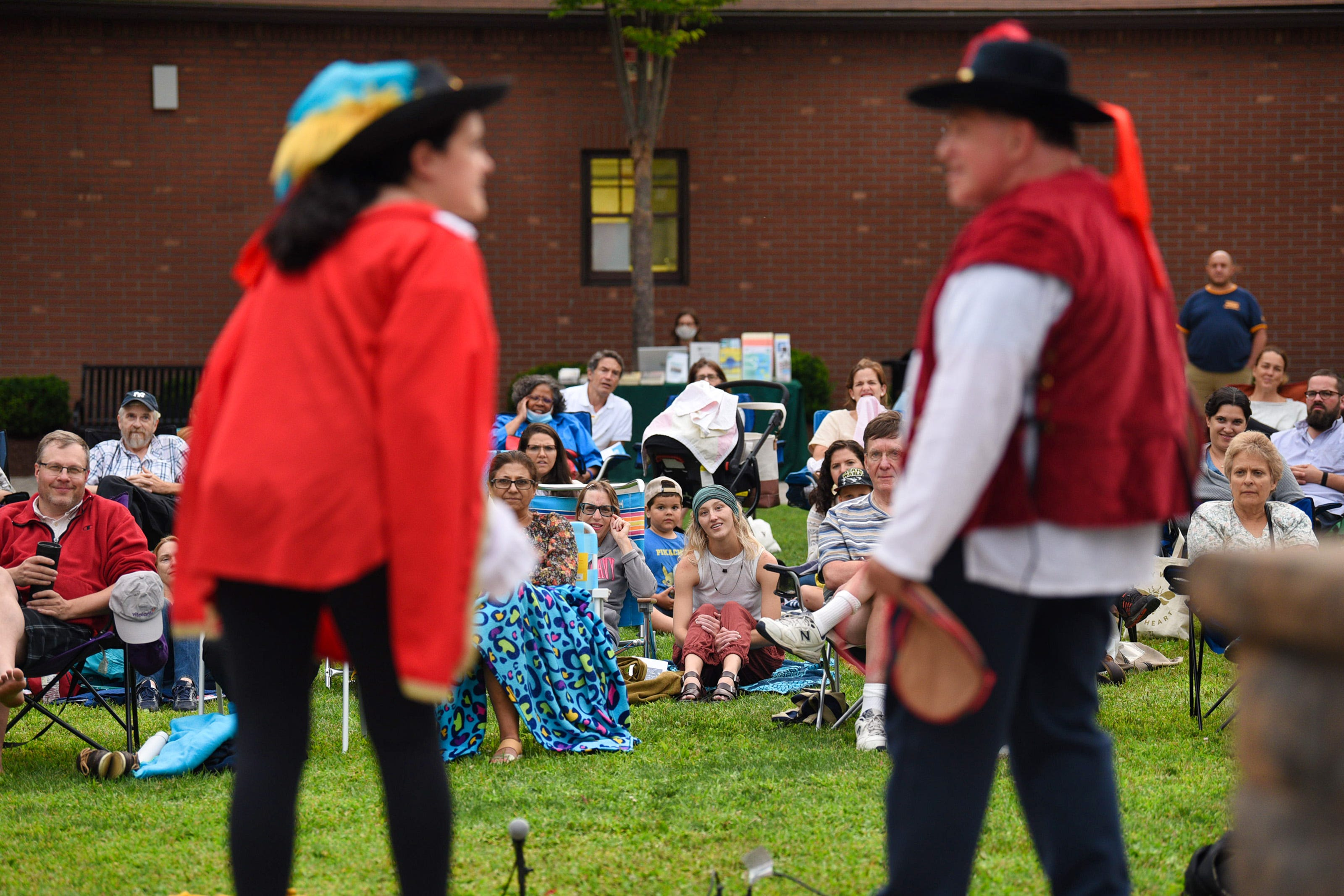 """The audience takes in the Hudson Shakespeare Company's performance of """"Twelfth Night"""" at Atlantic Street Park just outside of Hackensack Performing Arts Center in Hackensack on 08/04/21.  The actors are Ashley Robyn Patten, left, and Jon Ciccarelli, right."""