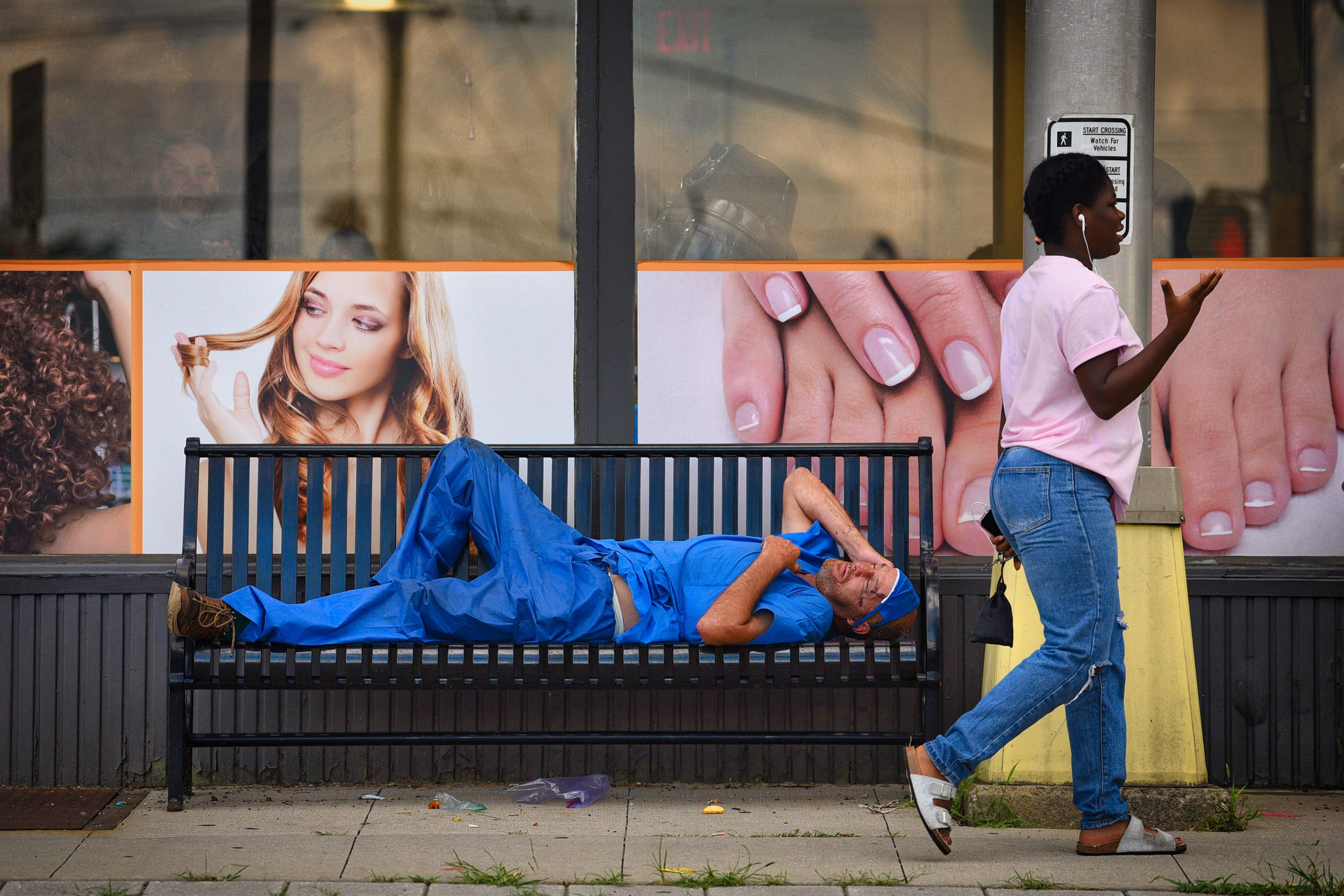 An unidentified man in hospital scrubs rests on a bench outside of a beauty salon at the corner of Main and East Anderson streets as a woman walks by talking on her phone in Hackensack. Photographed on 07/18/21.