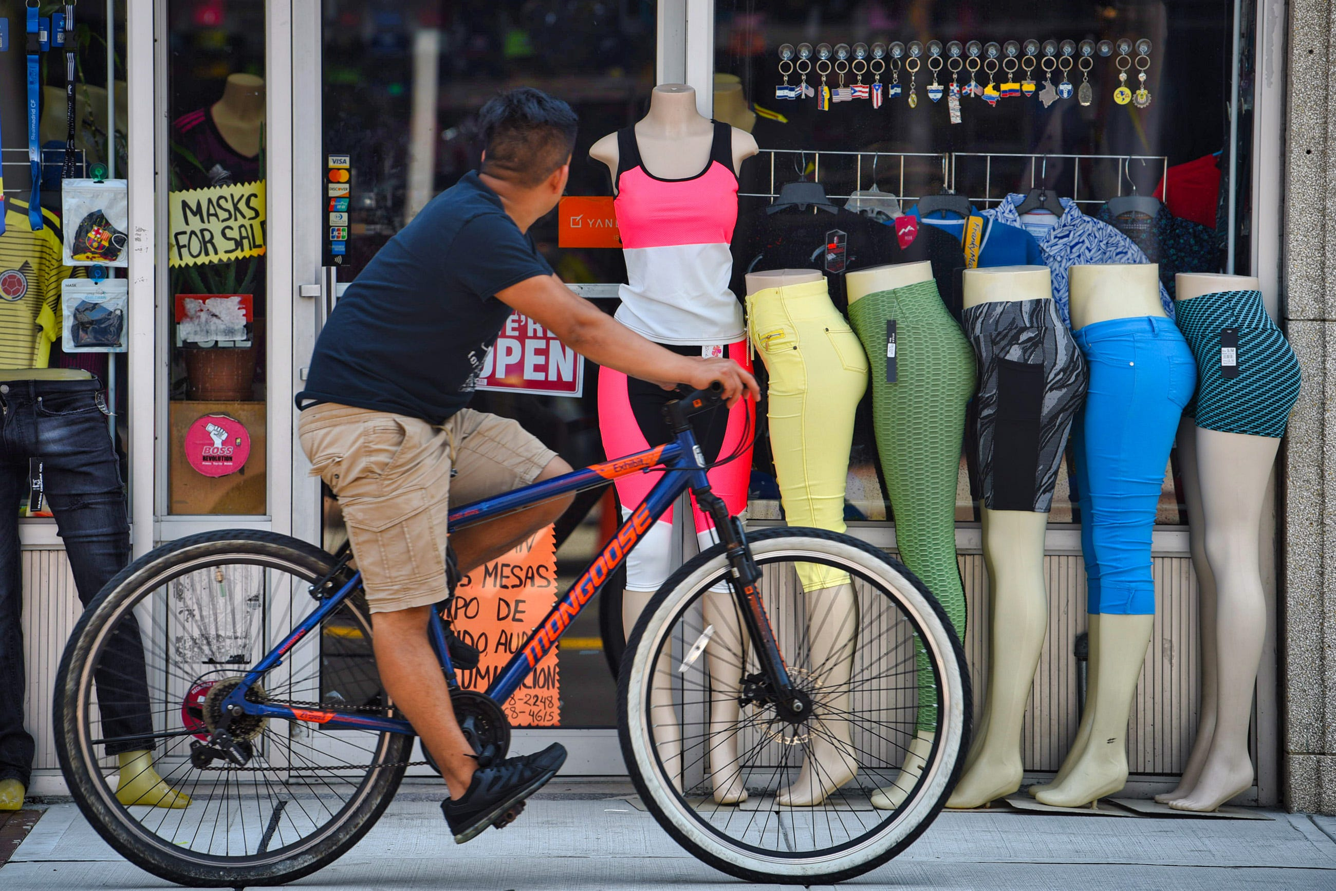 A man on a bicycle looks at colorful mannequin legs displayed outside of the Yambao Records located along Main Street in Hackensack on 07/18/21.