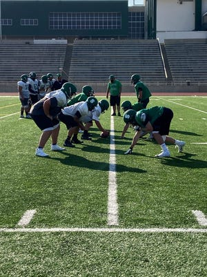 Members of the Farmington Scorpion offensive and defensive lines prepare for Friday's season opener on the road against the Roswell Coyotes