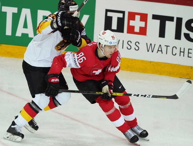 Janis Moser of Switzerland, right, and Tom Kuhnhackl of Germany battle for the puck during the Ice Hockey World Championship quaterfinal match between the Switzerland and Germany at the Olympic Sports Center in Riga, Latvia, Thursday, June 3, 2021. (AP Photo/Oksana Dzadan)