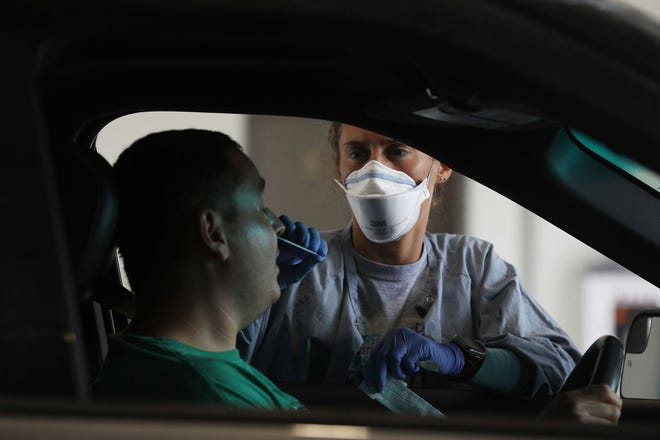 Ashley Randolph administers a COVID-19 test at the Blessing Express Clinic, a drive-thru site, on July 8, 2021, in downstate Quincy. The clinic, run by Blessing Health System, was previously a Sears tire center and renovated to deliver medical services in January. (John J. Kim/Chicago Tribune/TNS)