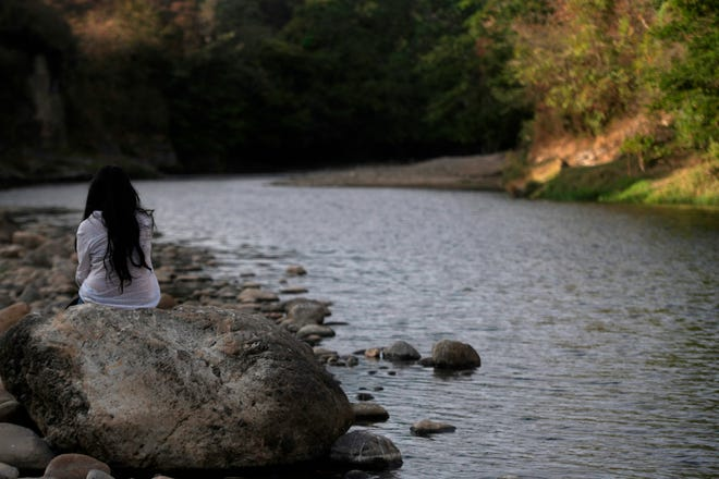 A woman sits on the banks of the polluted Lempa River in Pinuelas, Honduras, on January 11, 2019. (Marvin Recinos/AFP/Getty Images/TNS)