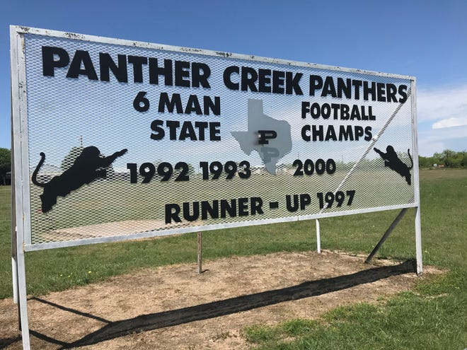 The Panther Creek High School football program's accomplishments are displayed on a sign outside the school.