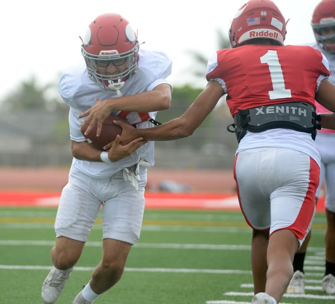 Running back Justin Barreto takes a handoff from quarterback Stanley Espinoza during the Hueneme High football team's practice on Tuesday, Aug. 17, 2021.