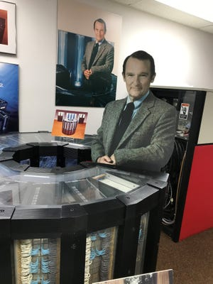 A life-size cutout of Seymour Cray leans against an early version of a supercomputer he designed at the Chippewa Falls Museum of Industry and Technology.