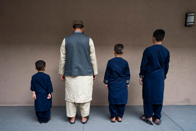 A newly arrived Afghan SIV holder stands for a portrait with three of his son in Sterling, Va., Tuesday, August 17, 2021.